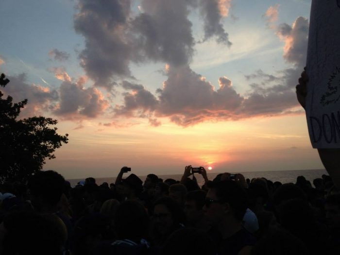 Thousands of students wait  for the College Game Day Broadcast to begin as the sun rises over Lake Michigan